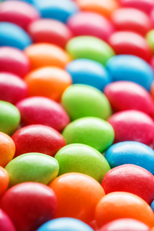 Rainbow colors of multicolored candies close-up, texture and repetition of dragee. Background Banco de Imagens