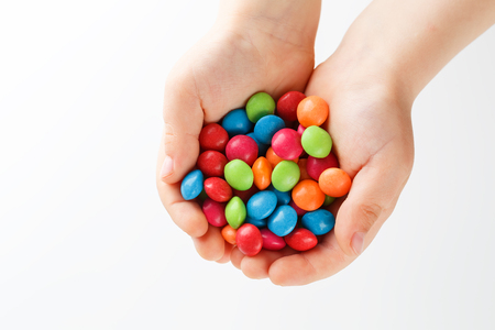 Multicolored candies in the hands of a child on a white isolated background. Rainbow colors in round drops, bright colors and an explosion of taste. View from above