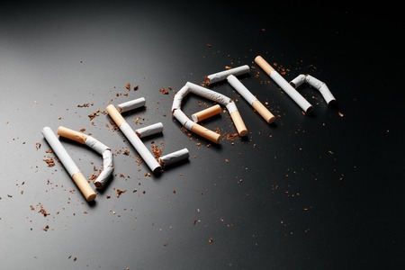 The inscription DEATH from cigarettes on a black background. Stop smoking. The concept of smoking kills. Motivation inscription to quit smoking, unhealthy habit. Smoking as a deadly habit, nicotine poison, cancer and smoking