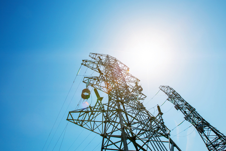 Power tower in the sky background, high-voltage post or high-voltage tower in the sunlight. High-voltage tower and electric power, high voltage