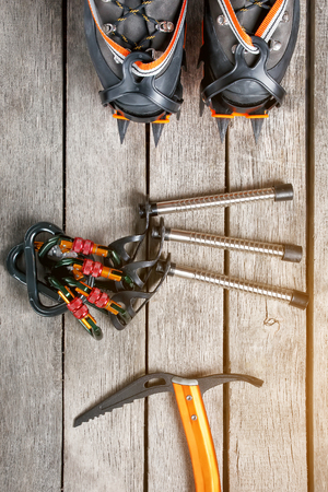 Top view of tourist equipment for a mountain trip on a rustic light wooden floor. Items include glasses, a card, a centipede, a carbine, an ice ax.