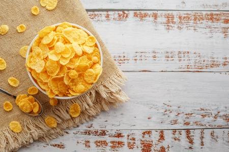 Recipiente con copos de oro sobre un mantel, sobre una mesa de madera clara, junto a una cuchara. Estilo rústico rústico. Vista desde arriba. Taza blanca, desayuno saludable de maíz por la mañana