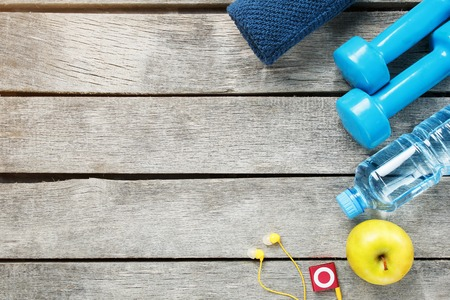Set of sports accessories for fitness concept with exercise equipment on gray background. Background view from above