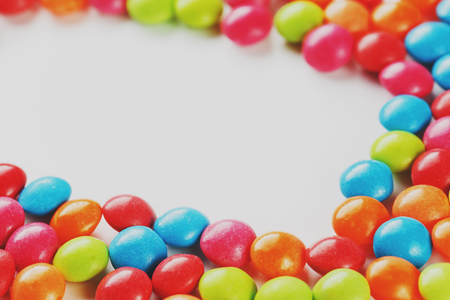 Frame of multi-colored candies close up. Rainbow colored dragee multicolored glaze on a white background. Bright colours Low contrast Stock Photo