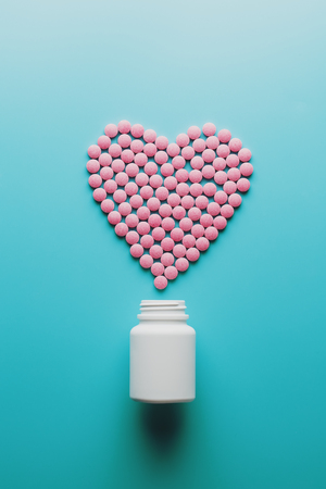 Pink B12 pills in the shape of a heart on a blue background, poured out of a white can. Food supplement concept