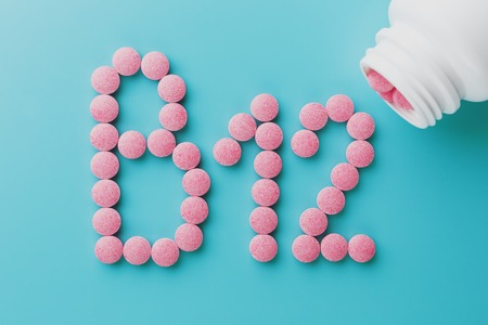 Pink pills in the shape of the letter B12 on a blue background, spilled out of a white can. Concept of dietary supplements