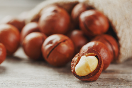 Macadamia nut on a wooden table in a bag, closeup, top view. Healthy product 스톡 콘텐츠