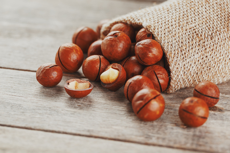 Macadamia nut on a wooden table in a bag, closeup, top view. Healthy product Stock Photo