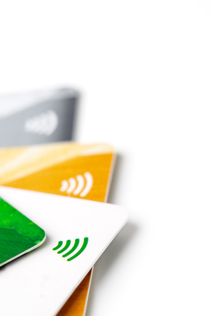 Credit cards with contactless payment. Pile of credit cards on white isolated background. Selective focus and close-up. Archivio Fotografico