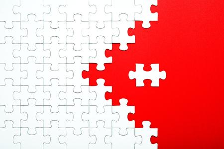 Pièces de puzzle blanches sur fond rouge séparées. Flèche de puzzle, concept de la direction et destruction du puzzle Concept pour les entreprises Banque d'images