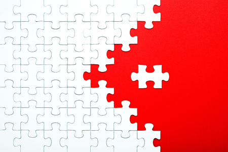 White puzzle pieces on a red background separated. Puzzle arrow, concept of the direction and destruction of the puzzle Concept for business Stock Photo