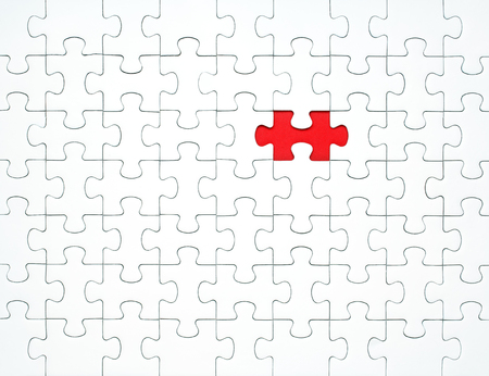 White puzzle pieces on a red background separated. Concept for business