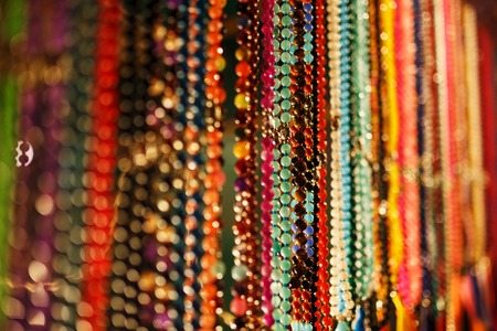 Colorful jewelry beads on the Indian night market, hang on the counter of Goa, India.