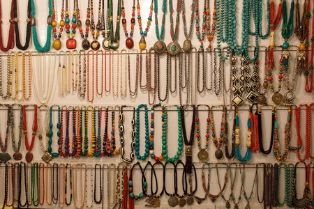 Colorful beads jewelry from Tibet night market, hang on the counter Goa, India. Stock Photo