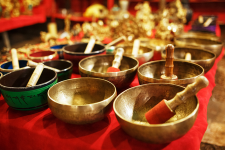 Golden Tibetan singing bowls on counters with red cloth of the night market Goa India