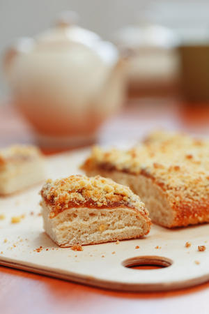 Sweet sand tart with apricot jam. Cut into pieces, lying on a board with a kettle in the background. Teapot with cups of tea with a sweet cake Imagens