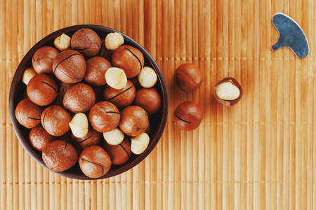 Macadamia nut on bamboo texture, concept of superfoods and healthy food. Overhead or top view shot Imagens