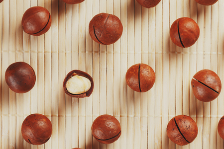 Flat composition with Australian macadamia nuts on bamboo light background. Patterns, repetitions. View from above Imagens