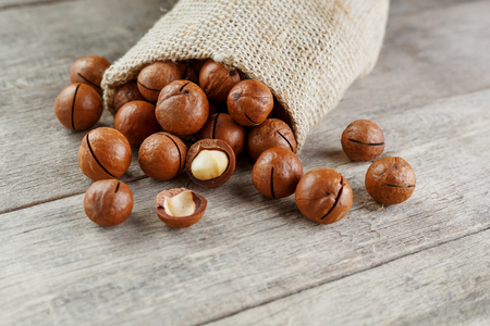 Macadamia nut on a wooden table in a bag, closeup, top view. Healthy product Imagens