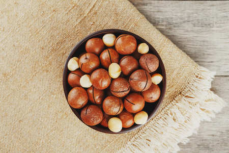 Macadamia nut on wooden background with vintage cloth, concept of superfoods and healthy food. Overhead costs or top view shot