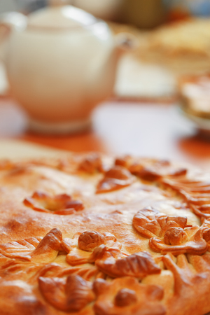 Russian pie with potatoes and mushrooms on the table. Freshly baked big cake decorated with flowers of their dough, traditional Russian pie