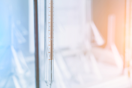 Measured scale for analyzing the quality of a liquid in a chemical laboratory, an instrument with equipment made of glass with blue liquid. Chemical experiments and tests