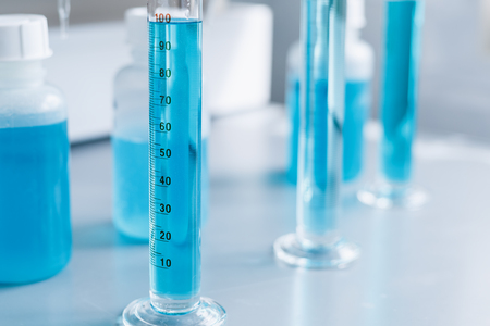 Analysis of the quality of liquids in a chemical laboratory, a device with equipment made of glass with a blue liquid, the hands of a scientist with close-ups