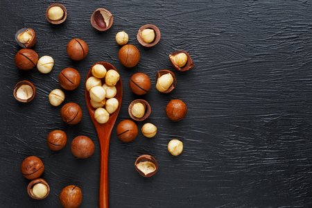 Shelled macadamia nut and peeled macadamia nut on a black textural background. The most expensive nut in the world, growing in Australia. top view and copy space