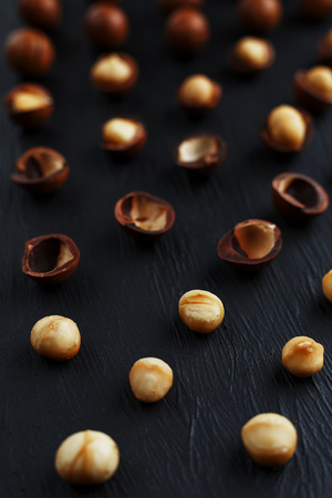 Purified and shell repeats macadamia nuts on black textural stone background. Healthy eating concept. The most expensive nut in the world, growing in Australia