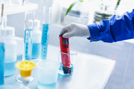 Analysis of water quality in a chemical laboratory, a device for measuring pH with equipment made of glass, the hands of a scientist with a red pH meter close-up Imagens
