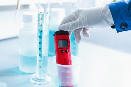 Analiza jakości wody w laboratorium chemicznym, urządzenie do pomiaru pH za pomocą aparatury wykonanej ze szkła, ręce naukowca z czerwonym pehametrem w zbliżeniu