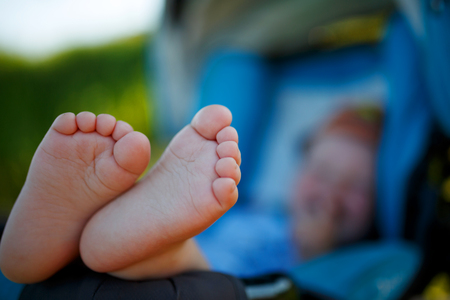 Cute, funny gentle heels of a child against the background of a lying in a stroller. Cheerful baby with cute heels in a stroller in nature