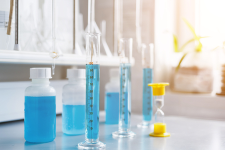 Analysis of water quality in a chemical laboratory, a device for measuring pH with equipment made of glass, the hands of a scientist with a red pH meter close-up Stock Photo
