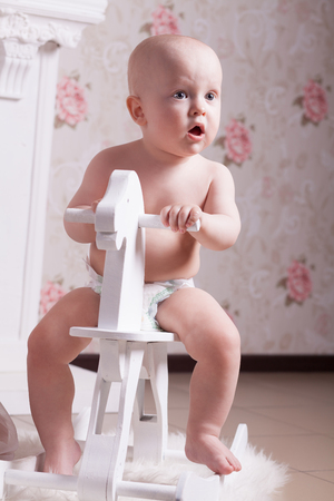 Funny baby in diapers is sitting on a white, wooden, toy horse and looks in surprise somewhere