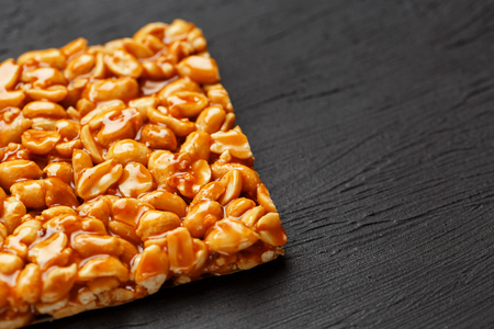 A large golden tile of peanuts, a bar in a sweet molasses on a black texture background. Kozinaki useful and tasty sweets of the East