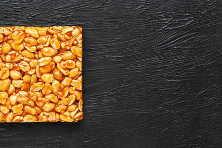 A large golden tile of peanuts, a bar in a sweet molasses on a black texture background. Kozinaki useful and tasty sweets of the East. View from above Reklamní fotografie
