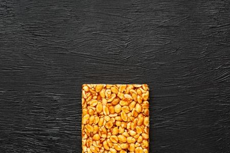A large golden tile of peanuts, a bar in a sweet molasses on a black texture background. Kozinaki useful and tasty sweets of the East. View from above