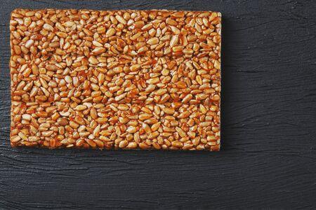 Useful snacks. Fitness diet food. Boletchik from kozinaki sunflower seeds, energy bars. Black textural background Top view. Copy space, low key Reklamní fotografie