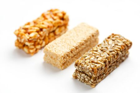 Grain granola bar with peanuts, sesame and seeds in a row on a white background. Top view Kozinaki Three assorted bars, isolate