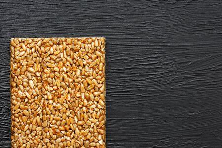 Useful snacks. Fitness diet food. Boletchik from kozinaki sunflower seeds, energy bars. Black textural background Top view. Copy space, low key Imagens