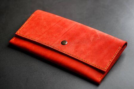 Portafoglio in pelle rossa su uno sfondo scuro vista dall'alto. Primo piano, dettagli della borsa, rivetto e firmware. macro