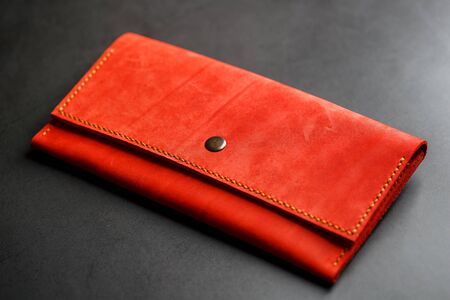 Red leather wallet on a dark background top view. Close-up, purse details, rivet and firmware. Macro