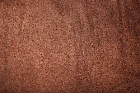 Brown velor textural background pattern. Gorgeous elastic velor fabric has a velvet pile, shine and texture. Volumetric background of velor fabric.