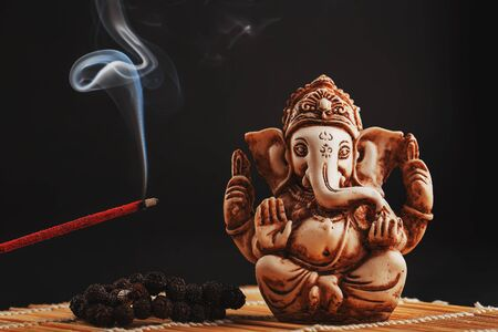 Hindu god Ganesh on a black background. Rudraksha statue and rosary on a wooden table with a red incense stick and incense smoke. Copy space