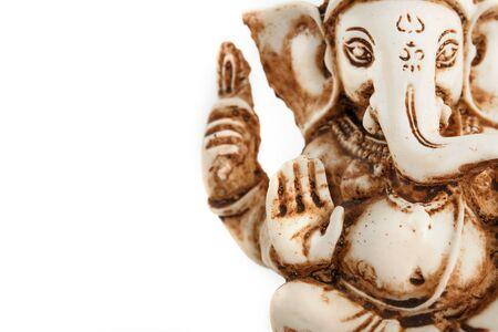 Hindu god Ganesh on a black background. Statue with incense smoke aromo sticks. Copy space