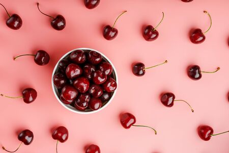 Cherry berry on a pink background in a white cup, top view. Concept of fertilization.