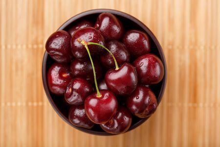 Ripe and juicy cherry berries on a wooden background in a brown cup. Top view, close-up.