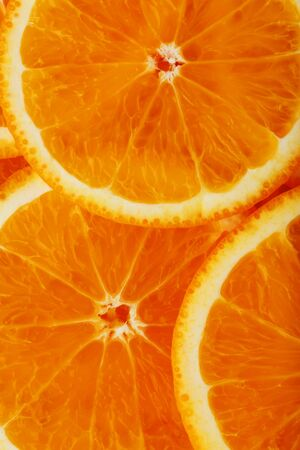 Slices of ripe orange backlit as a textural background. Full screen, close-up