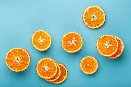 Fette e fette di polpa d'arancia su uno sfondo blu brillante come sfondo strutturale, il substrato. Schermo intero Piatto, vista dall'alto. Sfondo di cibo. Modello di agrumi. Pop art, piatto, vista dall'alto