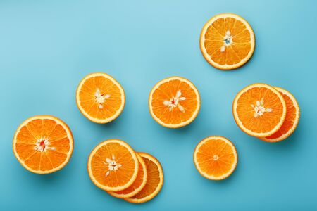 Slices and slices of orange pulp on a bright blue background as a textural background, the substrate. Full screen Flat lay, top view. Food background. Citrus pattern. Pop art, flat lay, top view 版權商用圖片